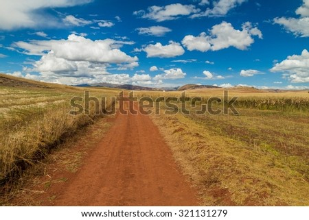 Road in cereal fields near Maras village, Sacred Valley, Peru - stock photo