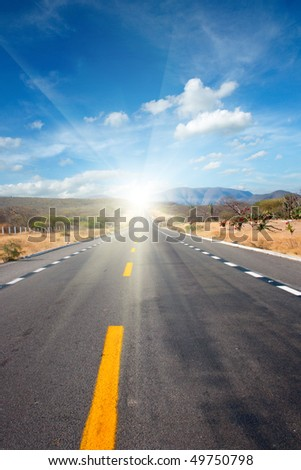 Road in desert  leading to sun - stock photo