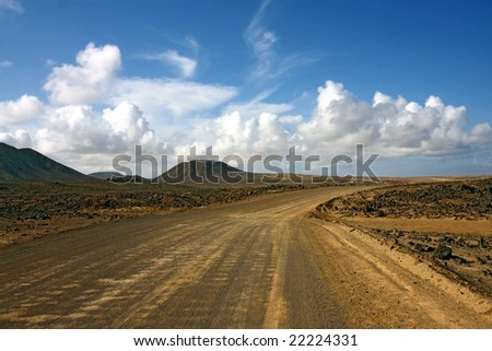 road in desert ,sky with clouds