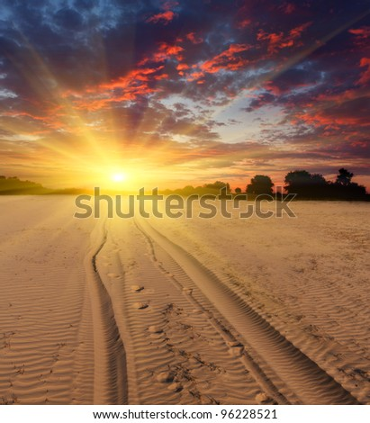 road  in desert with sunset background - stock photo