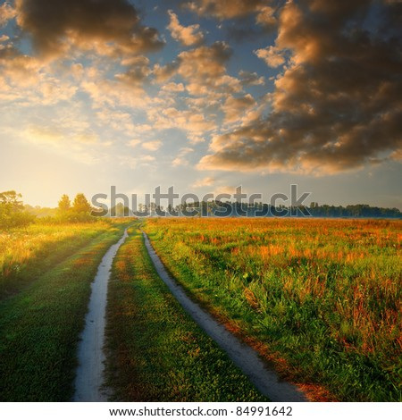 road in field and cloudy sky at sunrise time