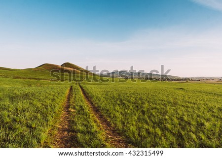 Road in green field. Evening. In the background the hills - stock photo