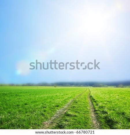 road in green village field - stock photo