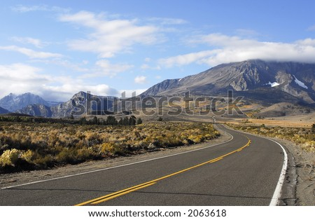 road in high desert leading to fall mountain scenery - stock photo