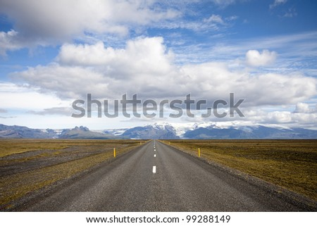 Road in Iceland with on the horizon mountains and glaciers - stock photo