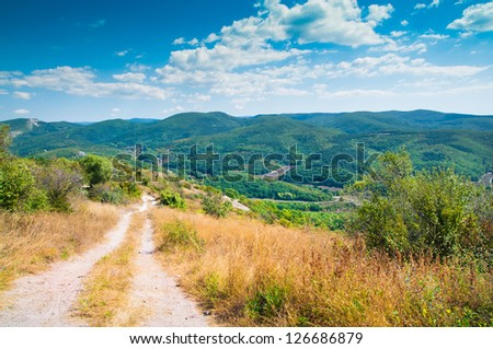 Road in mountains at blue sky - stock photo