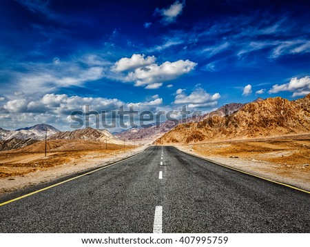 Road in mountains Himalayas and dramatic clouds on blue sky. Ladakh, Jammu and Kashmir, India - stock photo