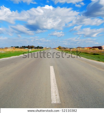 Road in perspective with blue sky and white clouds all in motion