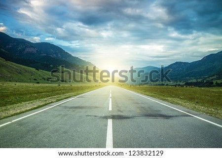road in summer mountains to the sunset - stock photo
