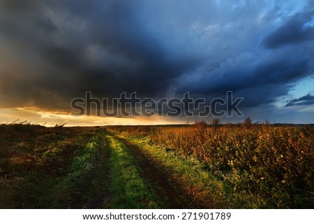 Road in the field and the dark dramatic rain clouds. Autumn in Latvia. - stock photo