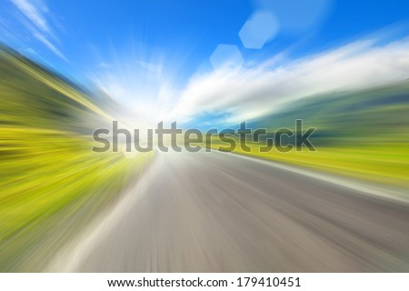 road in the mountains, a blurred image with patches of sunlight - stock photo