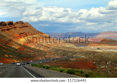 Road in USA with grass on the sides, hills in the background. - stock photo