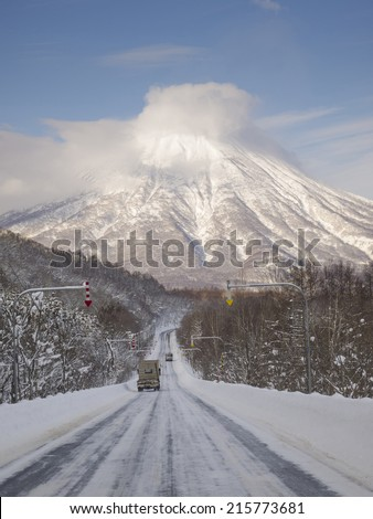 Road in winter which continues to Mt. Yotei, an active stratovolcano located in Shikotsu-Toya National Park, Hokkaido, Japan. It is one of the 100 famous mountains in Japan. - stock photo