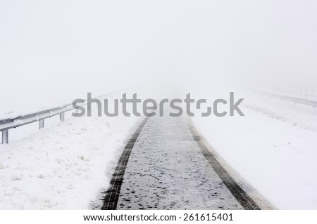 road in winter with snow and car track - stock photo