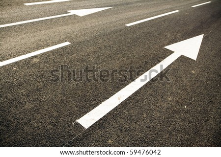 Road lanes with arrow markings at sunset - stock photo