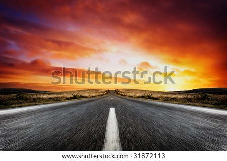 Road leading into a beautiful sunset - stock photo