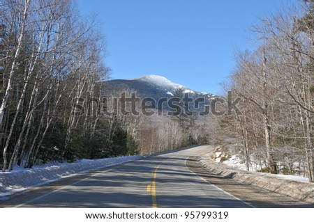 Road leading through Grafton Notch with a snow capped mountain in the distance - stock photo