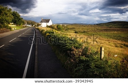Road leading to chapel at wide field embedded in mystical ambiance, Isle of Skye, Scotland - stock photo