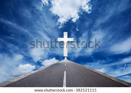 Road leading to glowing cross - stock photo
