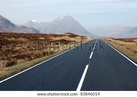 Road leading to the mountains of Scotland - stock photo