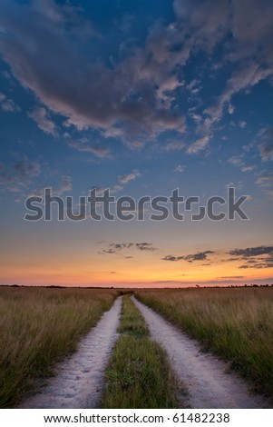 Road leading towards a sunset over the Kalahari desert - stock photo