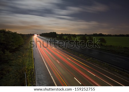 road light trails at night on motorway - stock photo