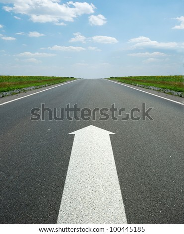road marking arrow. White arrow at detailed texture asphalt