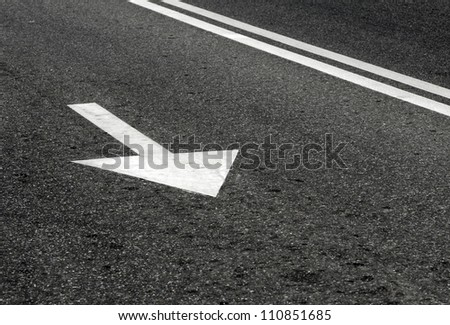 Road marking on asphalt in the form of an arrow - stock photo