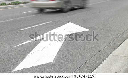 Road marking white arrow on gray asphalt street surface. Pointer indicates traffic lanes merging. Fast moving car in background. Motion blur. Perspective view.  - stock photo