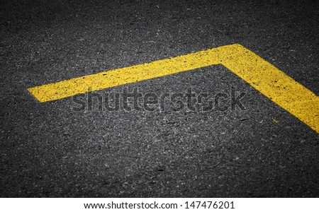 Road marking with yellow lines on dark asphalt - stock photo