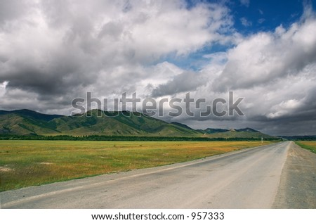 Road, mountains and skies - stock photo