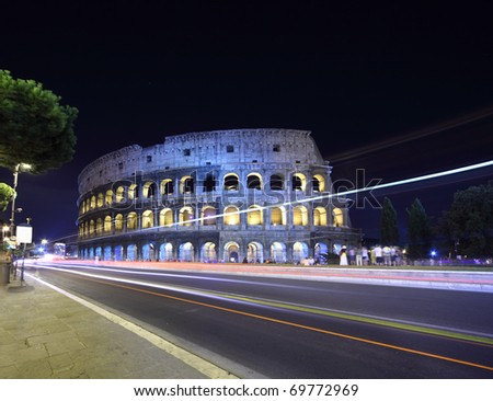 road near old stone walls of Coliseum at summer night in Rome, Italy - stock photo