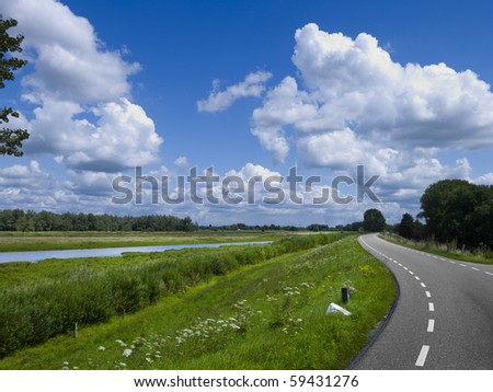Road on a dike in a Dutch landscape with the river the Merwede near the old town of Woudrichem, province Noord-Brabant - stock photo