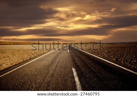 Road on dry land and the golden sky - stock photo