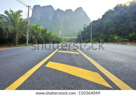 road on field and forest. - stock photo