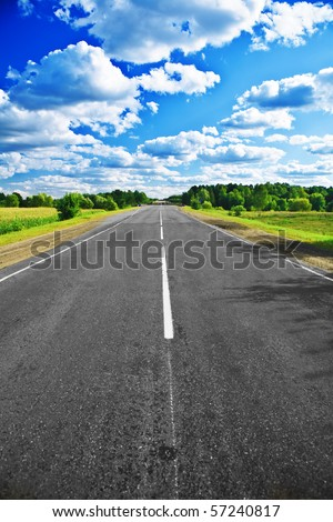 road on field and forest - stock photo
