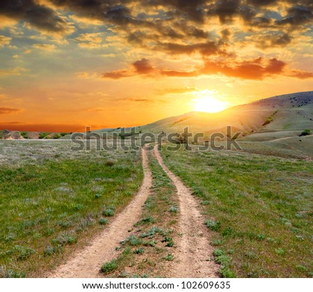 Road on green meadow in mountains on sunset background
