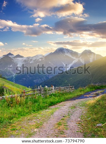 Road on green meadow on background of the high mountains and bright sky during sundown. Composition of the nature - stock photo