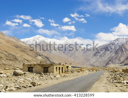 Road on plains in Himalayas with mountains - stock photo