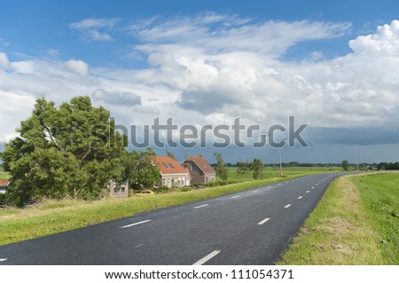 road over a dyke in a typical dutch polder landscape - stock photo