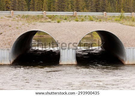 Road over dual culvert pipe infrastructure bridge strong current flow of river water tunnel through