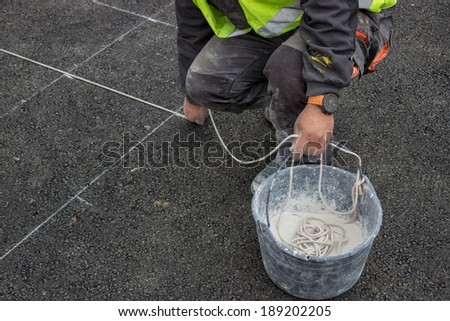 road paint worker with chalk line, string covered in chalk dust. ping a chalk line to mark a line down and preparing for marking new road lines