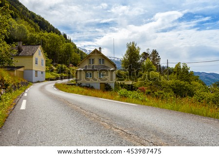 road passes alongside traditional Norwegian wooden houses, Norway