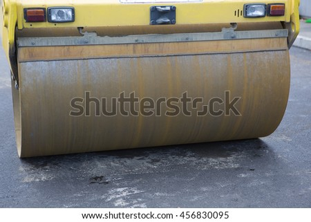 Road Paving Construction, asphalt roller closeup. Workers laying stone mastic asphalt during street repairing works. Worker making asphalt with coated chippings.  - stock photo