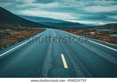 Road perspective in overcast weather. Norway landscape. Film style dramatic colors. - stock photo