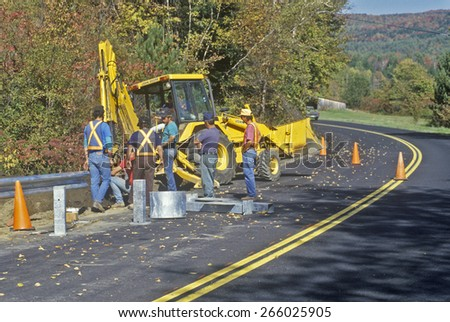 Road Repair workmen with Caterpillar tractor and cones, New England - stock photo