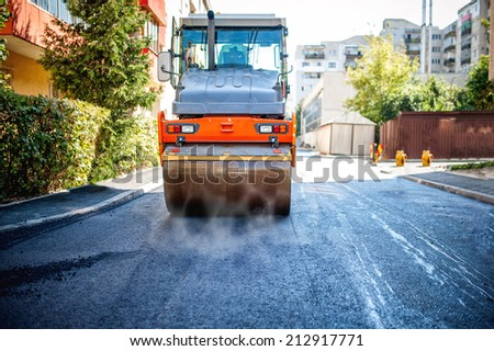 road repairing in urban modern city with heavy vibration roller compactor - stock photo