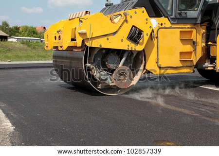 Road roller  at a road construction site - stock photo