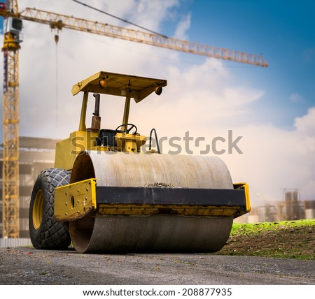 Road roller at construction site with cloudy blue sky - stock photo