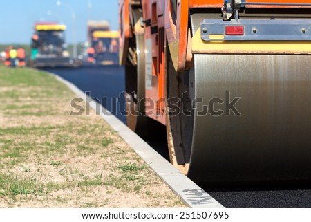 Road roller compacting asphalt  near curb stone - stock photo